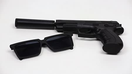 pistola : The gun with a silencer and black glasses