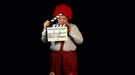 film slate : Clown with a movie clapperboard Stock Footage
