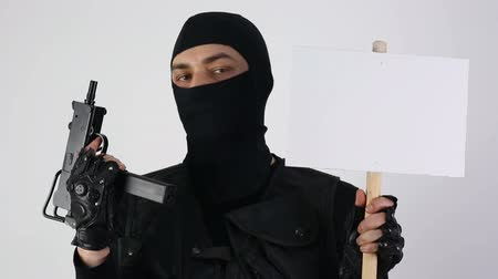 terrorizmus : Terrorist with submachine gun and sign on white background Stock mozgókép
