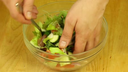 Mixing fresh salad
