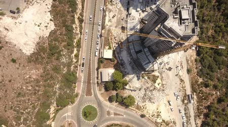 palmo : A flight over the Haifa quarter, lone cars passing through the streets, 2 exhausted houses with construction cranes, a span over a construction crane.