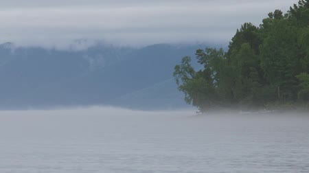 assombrada : A foggy evening over the river, waves splashing on a pebble beach, in the distance the forest blackens.