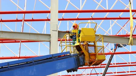 dach : construction worker working at construction site using lifting boom machinery Wideo