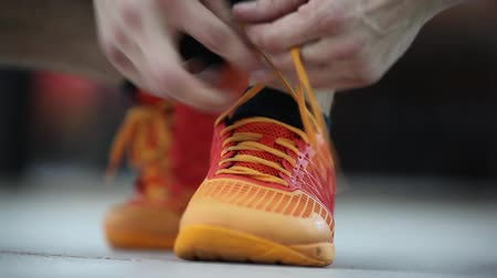 The athlete tying shoelaces on sneakers. Preparation for the exercise. Close-up.