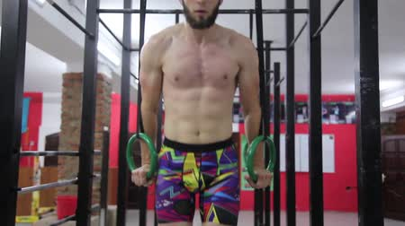 Young male doing ring dips at the gym Stock mozgókép