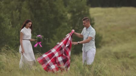 Couple in love spreads a blanket in a field. Stock mozgókép