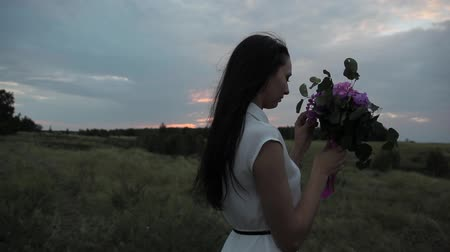 Girl with a bouquet in the field. Sunset.