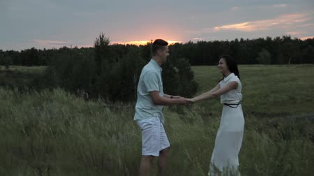 Lovers in the field. Guy hugs girl. Smile. Sunset.