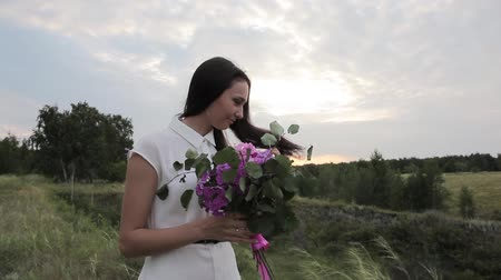 Girl with a bouquet in the field. Sunset. Flowers.