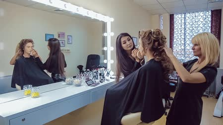 Make up artist doing professional makeup and hair stylist makes hairstyle of young woman Stock mozgókép