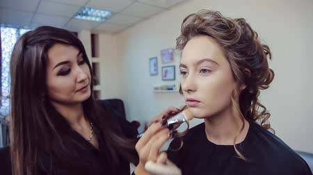 Make up artist doing professional makeup of young woman in beauty studio