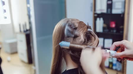 Hair stylist makes professional hairstyle using curling irons of young woman in beauty studio Stock mozgókép