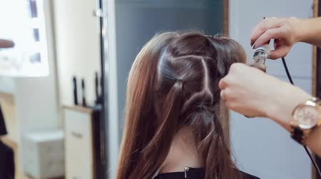 Hair stylist makes professional hairstyle of young woman using curling irons in beauty studio