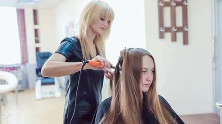 Hair stylist makes professional hairstyle of young woman in beauty studio
