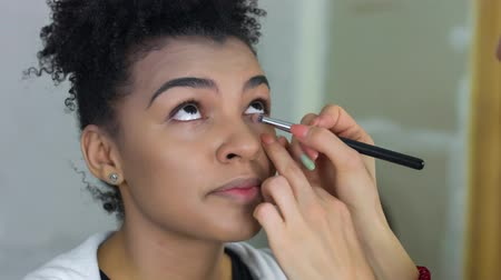 arcszín : Professional make-up artist makes makeup of afro-american model. Beauty and fashion concept. Stock mozgókép
