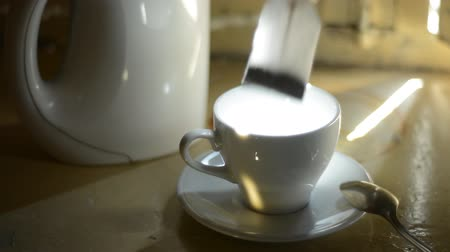 teabag : Tea bag in a cup. Put into a clean empty white paper bag cup of tea. A beam of light illuminates the cup of tea on the window sill Stock Footage