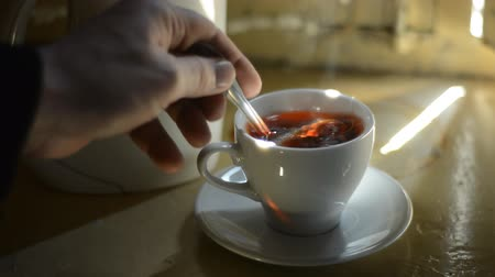 black tea : Stir in a cup of tea with a spoon. A beam of light illuminates the cup of tea on the window sill
