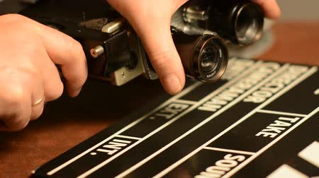 film slate : We change the lens on a retro film camera. Movie clapper lie with retro camera and movie films on reels. film Production Stock Footage
