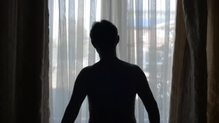 unveil : Man with a backlight opens the curtains in the morning. The person opens the curtains and stretches the arms.