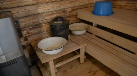 rendelenmiş : Russian bath with round logs. Interior of a bath with a wood stove and wash basins