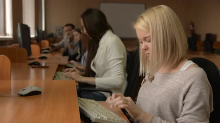 questionário : Portrait of a cheerful female student working on the computer. A group of young people in a computer classroom. Young business woman smiling Stock Footage