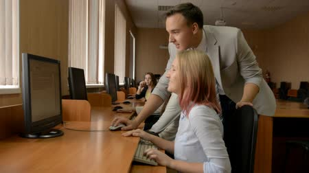 questionário : Young man is helping a blonde working on a computer. Young people solve the problem together in the computer room