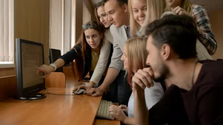questionário : Young people solve problem together in computer room. A group of cheerful business students look at the monitor and discuss the task Stock Footage
