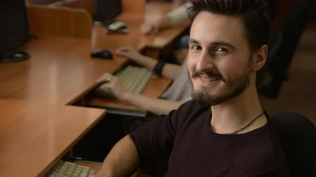 questionário : Portrait of a young man with a beard smiling. A business man is working at a computer. Students doing computer class. People in the office at work. Stock Footage