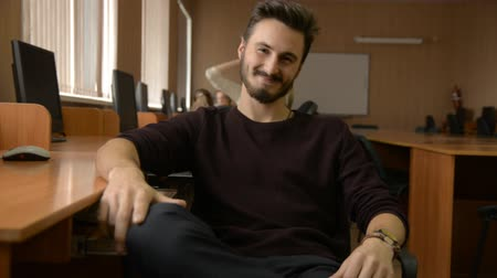 questionário : Portrait of a young man with a beard. Business man sitting in a chair with a computer