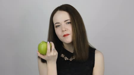 césar : Charming young woman with green apple and smiles. Concept of eating fresh fruits vegetarian