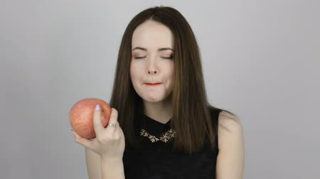 césar : Beautiful young woman with a pink apple and smiles. Concept of eating fresh fruits vegetarian