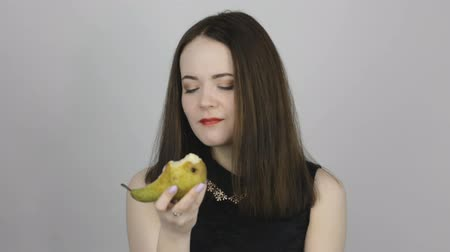 segurar : Beautiful young woman eats a green pear and smiles. Concept of eating fresh fruits vegetarian
