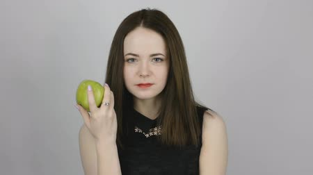 césar : Beautiful young woman eats a green apple. Concept of eating fresh fruits vegetarian Stock Footage