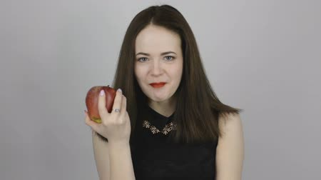 césar : Cheerful young woman eating a red apple. The concept of eating fresh fruits is vegetarian. A girl eats a fruit on a white background