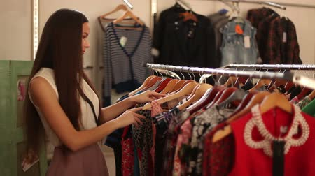 ruházat : Girl chooses clothes and looks in the mirror