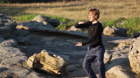 stay active : A young man among the large rocks performing Tai Chi gymnastics. Healthy lifestyle. Stock Footage