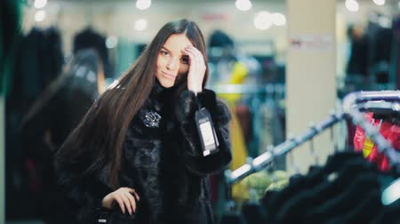 мысль : Beautiful brown-haired girl chooses a fur coat in the store. Shopping. Series.