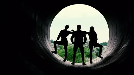industrialization : Silhouettes of young people on the background of a large hole.
