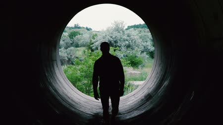 industrialization : Silhouette of a young man approaching the camera on the background of a huge hole.