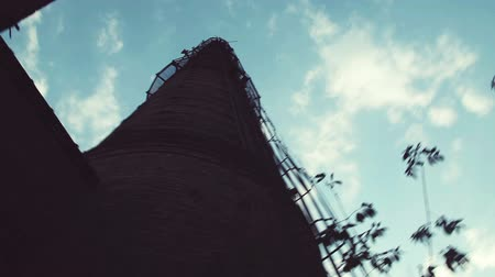 defunct : Defunct industrial brick chimney against bright blue sky