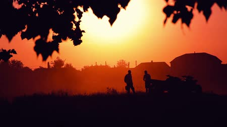 atv : Silhouettes of men and ATVs at sunset. Stock Footage
