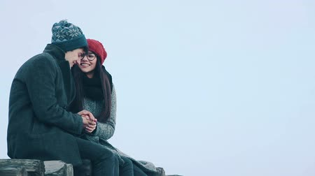warms : Loving couple sitting on a wooden bridge, on a background of gray sky of snow, and talking.