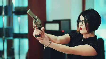 pistola : Girl brunette in glasses with black frames, aim at a target holding a gun.