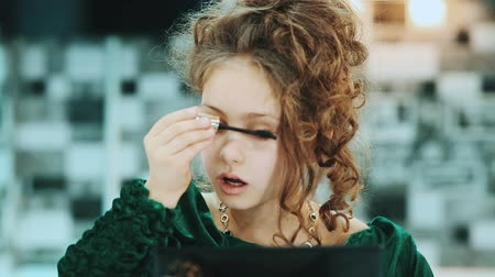 капелька : Cute little girl in a green dress color eyelashes sitting near a mirror. Стоковые видеозаписи