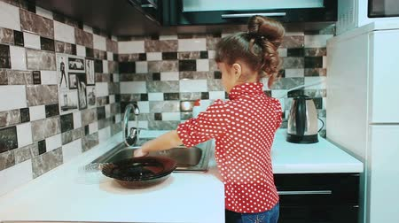 mutfak malzemesi : Little girl washing dishes in the kitchen.