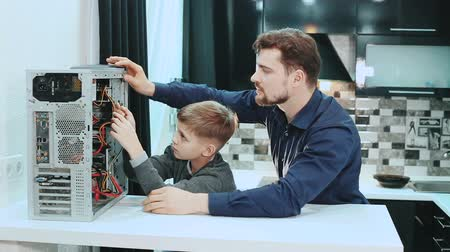 база : Father and son repair a computer.