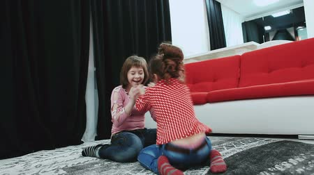 инвалидность : Two girls, one of them with Down syndrome, sitting on the carpet at home, play and have fun. Стоковые видеозаписи