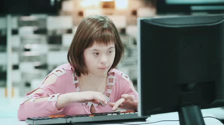 инвалидность : Girl with Down syndrome sitting at a computer at home and typing text.