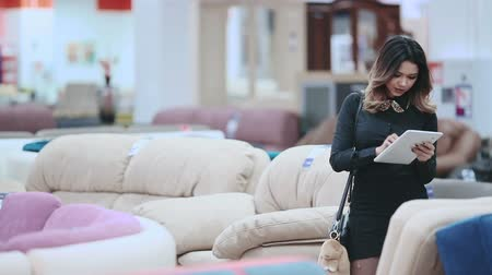 punčocháče : Attractive girl in a black dress, walking on the furniture store holding a tablet in hands.
