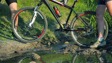 atividades de lazer : Couple crossing a stream together with their bikes in countryside